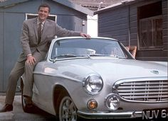 Roger Moore happily posing with his Volvo P1800, the car of Simon Templar, The Saint.