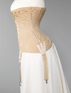 Cotton corset by Bon Marché, French, 1904-06. This corset perfectly illustrates the understructure required to accomplish the dominant S-curve silhouette of the time. It was purchased at the well-known Parisian department store Au Bon Marché in 1904. The front-lacing, as opposed to the usual back lacing, is highly unusual for this period. It became a more popular feature for corsets later in the 20th century, as it allowed a woman to put on and adjust the corset by herself.