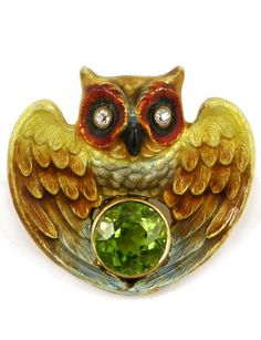 19th century enamelled gold, diamond and peridot owl brooch, American c.1880, of heart shaped outline, the gold wings open and with shaded transluscent enamelling, centred by a round peridot, diamond set eyes