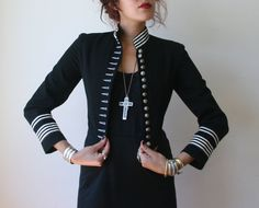 Awesome little black military jacket with silver stripes on the cuffs and collar. Has collar closure, 15 silver shield and eagle buttons and a