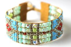 This loom beaded bracelet is handmade on a bead loom with turquoise, mint and cherry red fire polished crystals and Japanese seed beads. The metal