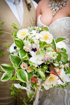 lush bouquet with feather accents // photo by Swoon Over It // View more: http://ruffledblog.com/romantic-terrain-wedding/