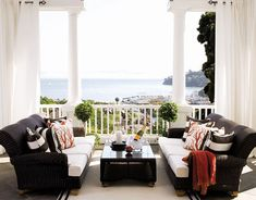 A Black and White Casual Porch  A pair of wicker sofas from Restoration Hardware suits this classic porch, which is just off this home's living room. Pillow fabrics are Stripe in Chocolate Kiss by Perennials and Mari in Coral by Lulu DK. Casual and cozy!