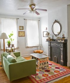 Green sofa, colorful rug, cool coffee table, a fireplace and a ceiling fan
