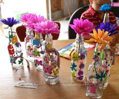 Easy Birthday party craft idea- decorate recycled bottles with stickers, ribbon, and rhinestones to make a flower vase