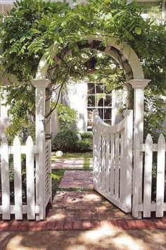 Pretty white picket fence and wisteria covered arbor gate. Love the brick pathway too!