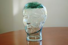 This is a funky vintage clear green glass head statue that makes a great display piece on its own or use it as a styling mannequin for a hat!