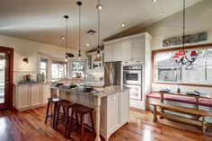 Country Kitchen with Pendant light, Flat panel cabinets, Breakfast bar and window seat dining area.