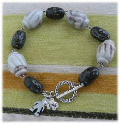 R38- Pulseira com peças cerâmicas, fecho metálico e peças metálicas com uma imagem   de um menino e um elefante.  5€