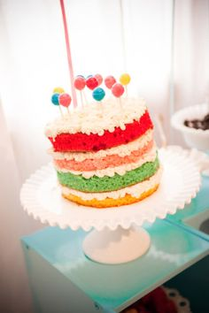 cute cake! white icing between the rainbow layers & suckers for decorations look like little balloons!