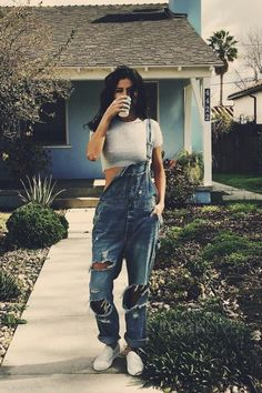 Selena Gomez wearing Kimchi Blue Blue Fuzzy Croptop, BDG Denim Overalls, Vans Classic Slip On Sneakers