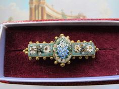 This is a beautiful antique Micro Mosaic brooch depicting white and blue flowers. In the center is an oval with a bunch of blue flowers with green