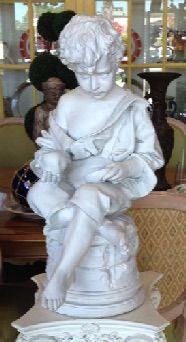 "Cast plaster version of 19th C statue of a boy holding an apple. He is dressed in an over-sized, is barefoot and seated on a stone seat. 12"" x 14"" x 24"" overall height. Display him on one of our pedestals."