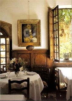 La Colombe d'Or, Paris. Love the different shaped windows, white tablecloths, flowers, painting on the wall, and the real wooden wainscot ain't too shabby either!