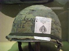 """Vietnam War Helmet. For those who served, """"US troops believed that Vietnamese traditions held the symbolism of the spade to mean death and ill-fortune, and in a bid to scare away Viet Cong soldiers without a firefight, it was common practice to leave an ace of spades on the bodies of killed Vietnamese and even to litter the forested grounds and fields with the card."""""""
