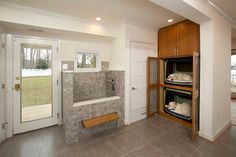 Dog friendly mud room, dog bed shelves, dog bath, stone tiles | Four Brothers LLC