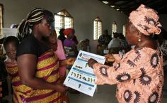 (At right) Taryonnoh N. Doe, vice president of Liberia United Methodist Women, shows an Ebola awareness poster as part of the UMW's anti-Ebola campaign.