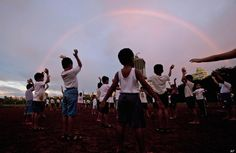 Rainbows  ~~   Children perform exercises in a park as a rainbow appears in the background in Mumbai, India, Saturday, Sept. 1, 2012. (AP Photo/ Rajanish Kakade)
