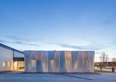 Perforated metal covers the facade of this office extension
