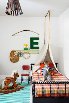 The clever bed canopy in Eli's space is simply a trio of humble hardware store staples: painter's drop cloth draped over a wooden dowel and hung from the ceiling with a thick manila rope.