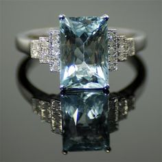 AN 18CT WHITE GOLD DECO STYLE AQUAMARINE AND DIAMOND RING; 3.06ct modified radiant cut aquamarine, four claw set, above stepped shoulders set with twenty diamonds,