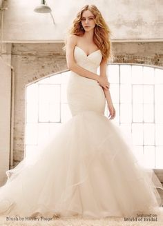 Ivory lace fit to flare bridal gown, sweetheart neckline and angel hair straps, full skirt of layered tulle with thin horsehair edging.