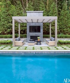 The poolside pergola features a Samsung outdoor television, sofas and ottomans by Crate and Barrel, and Pottery Barn tables   archdigest.com