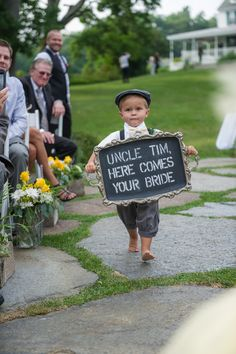 """Barefoot ring bearer wearing newsboy cap and suspenders while holding a chalkboard sign that said, """"Uncle Tim, here comes your bride."""""""