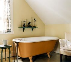 The vintage claw-foot tub in this kids' bathroom got a makeover courtesy of custom-mixed orange paint; bespoke shades of pea green and harvest yellow transformed the floors and walls. Ordinary glass vases masquerade as fancy display cases when bird silhouettes nest inside.   - CountryLiving.com