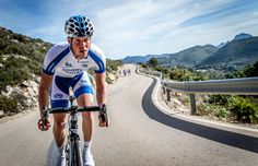 team novo-nordisk cyclist riding up a hill in team cycling kit