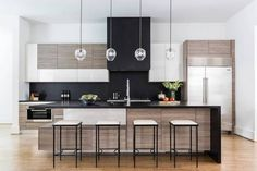 Contemporary kitchen with wood cabinents, black accents, and glass pendants