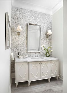 White and gray bathroom features a gray mosaic tiled accent wall lined with a white washstand fitted with diamond panel doors topped with grey and white marble under a beveled mirror illuminated by Greek key sconces, Visual Comfort Lighting Abbot Single Arm Sconces.
