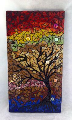 """Árvores remetem à natureza e é sempre bom trazê-la para perto de nós... Esse quadro que traz uma frondosa árvore, com muitas nuances de cores e brilho foi feito em uma base de MDF, com mosaico elaborado em pastilhas de vidro cristal e gemas de vidro. """"Árvores em festa"""" vai deixar qualquer ambiente de sua casa ou escritório mais charmoso e alegre. <br>Tamanho: 26 x 49 cm"""