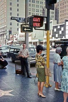 shops, cars, and pedestrians at the intersection of Hollywood & Vine, 1963