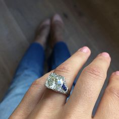 Art Deco engagement ring made in platinum and centered with an approximate 3.05 carat EGL certified bezel set old european cut diamond with K-L color and SI2 clarity. Accented with calibre cut sapphir