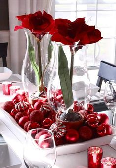 stilvolle Tischdeko mit roten Weihnachtskugeln in einer Platte und Vasen mit roten Blumen