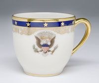 State dinner service of Franklin Delano Roosevelt (President 1933-1945)--After-Dinner Coffee Cup/Made in Trenton, New Jersey, United States, North and Central America c.1934--Made by Lenox Incorporated, Trenton, New Jersey, 1889 - present. Ordered from William H. Plummer and Company, New York. Hard paste porcelain, lead glaze, printed, enamel, and gilded decoration. 2 1/4 x 3 5/16 x 2 9/16 inches (5.7 x 8.4 x 6.5 cm)