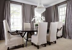 Sophisticated dining room features gray paint on upper walls and gray wainscoting on lower walls framing windows dressed in gray silk curtains.