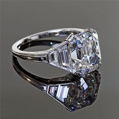 Cushion cut flanked by custom cut trapezoid side stones. Exquisite.