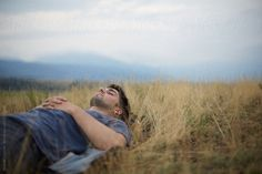 Young man laying and resting on the grass of a field by Miquel Llonch