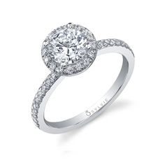 This classic halo engagement ring features a one carat round brilliant diamond center with a total of 0.25 carats of diamonds surrounding the center stone and going down the shank. Classic and Simple Engagement Ring with round diamond. Sylvie Engagement Rings. Double Halo Engagement Ring, Classic Engagement Rings, Halo Rings, Round Diamonds, Classic Style, Brilliant Diamond, Stone, Metal, Gold