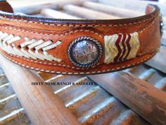 Vintage leather cuff with rawhide braiding/lace featuring brass cross concho.