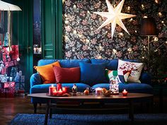 An IKEA STOCKSUND blue sofa in a Christmas-style living room with a STOCKHOLM coffee table, some VINTER candles and a big star-shaped STRALA lamp