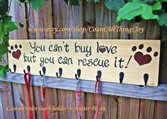 "Custom Leash Holder!  Keep your leashes and collars organized with the hooks on this sign. ""You Can't Buy Love But You Can Rescue it!"" (Actually, I can convert ANY of my signs to leash holders) Hand painted wooden sign, approximately 30""x7"". Four black hooks come standard for hanging leashes, collars, bandanas and more. Available at Count All Things Joy,  https://www.etsy.com/listing/188829940/leash-holder-custom-breed-and-color-all"