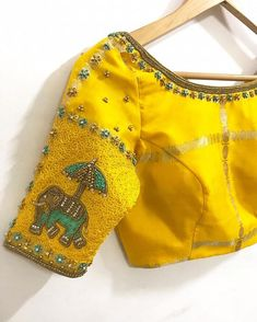 Stunning sunshine yellow color designer blouse with elephant ambari design hand embroidery thread and kundan work on sleeves. Blouse with floral design hand embroidery work on neckline. Pattu Saree Blouse Designs, Blouse Designs Silk, Designer Blouse Patterns, Bridal Blouse Designs, Simple Blouse Designs, Stylish Blouse Design, Simple Designs, Indie, Bollywood