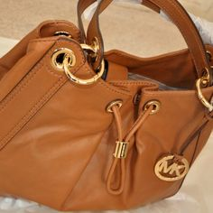 """Authentic Michael Kors Ludlow Bag Gently used 100% authentic bag, minor scratches on the bottom of the bag but overall in good condition. Inside is in perfect shape with no stains. Leather with gold hardware. 2 inside compartments separated by a middle zipper compartment. 2 side pockets. Measures approx 14"""" x 6"""" x 9"""" with a 8"""" strap drop. I do not trade, sorry! Price is firm unless bundled. Michael Kors Bags"""