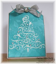 handmde Christmas card ... tag shape .. turquioise watercolor look background ... white embossed filegre tree ... silver bow and rhinestones ... luv it!! ... Hero Arts ...