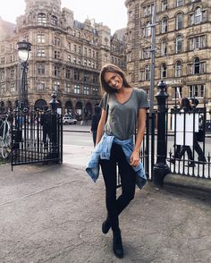 Minimal casual chic style - grey tee, black skinny jeans, booties and denim jacket tied around the waist