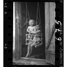 A girl and a boy in a doorway swing | The Lodz Ghetto Photographs of Henryk Ross | AGO