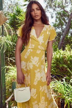 Win them over with the Heart of Marigold Yellow Floral Print Wrap Maxi Dress! Floral print maxi dress with a surplice bodice, fluttering short sleeves, and a wrap skirt.